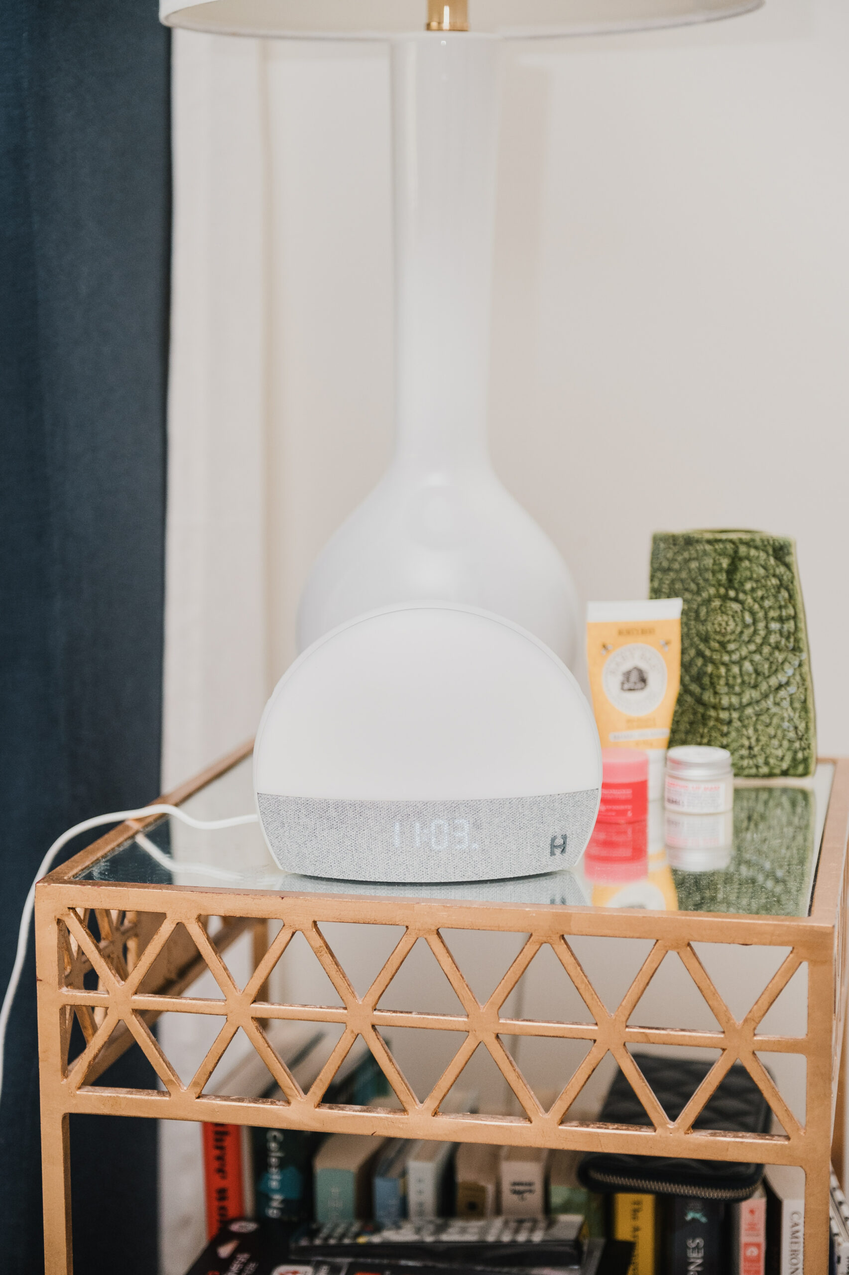 bedside table with Hatch Restore, lamp, skincare products, and books