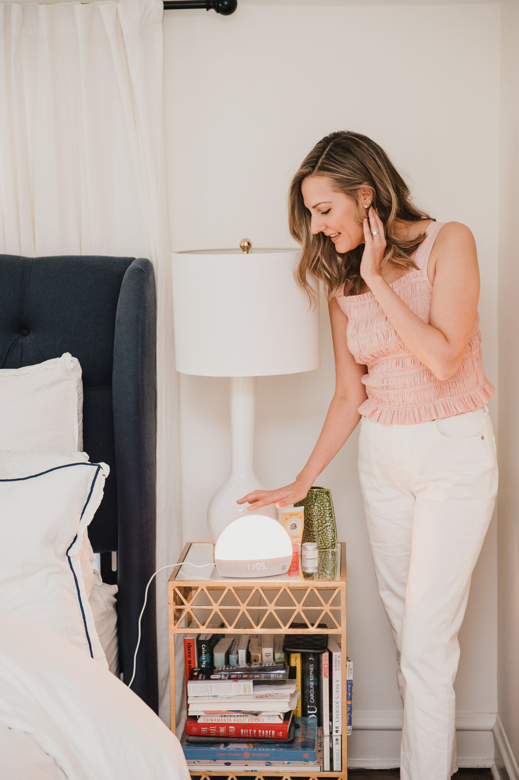 woman standing near her bedside table with Hatch Restore, lamp, skincare products, and books