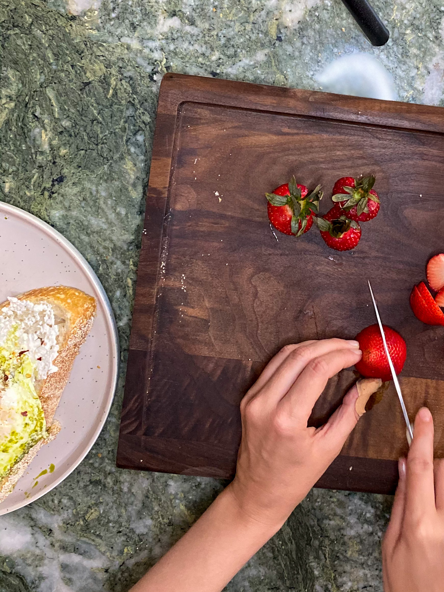 woman slicing strawberries on a chop board