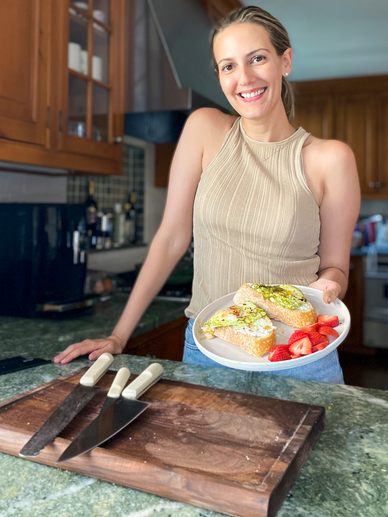 woman smiling and holding a plate out with food