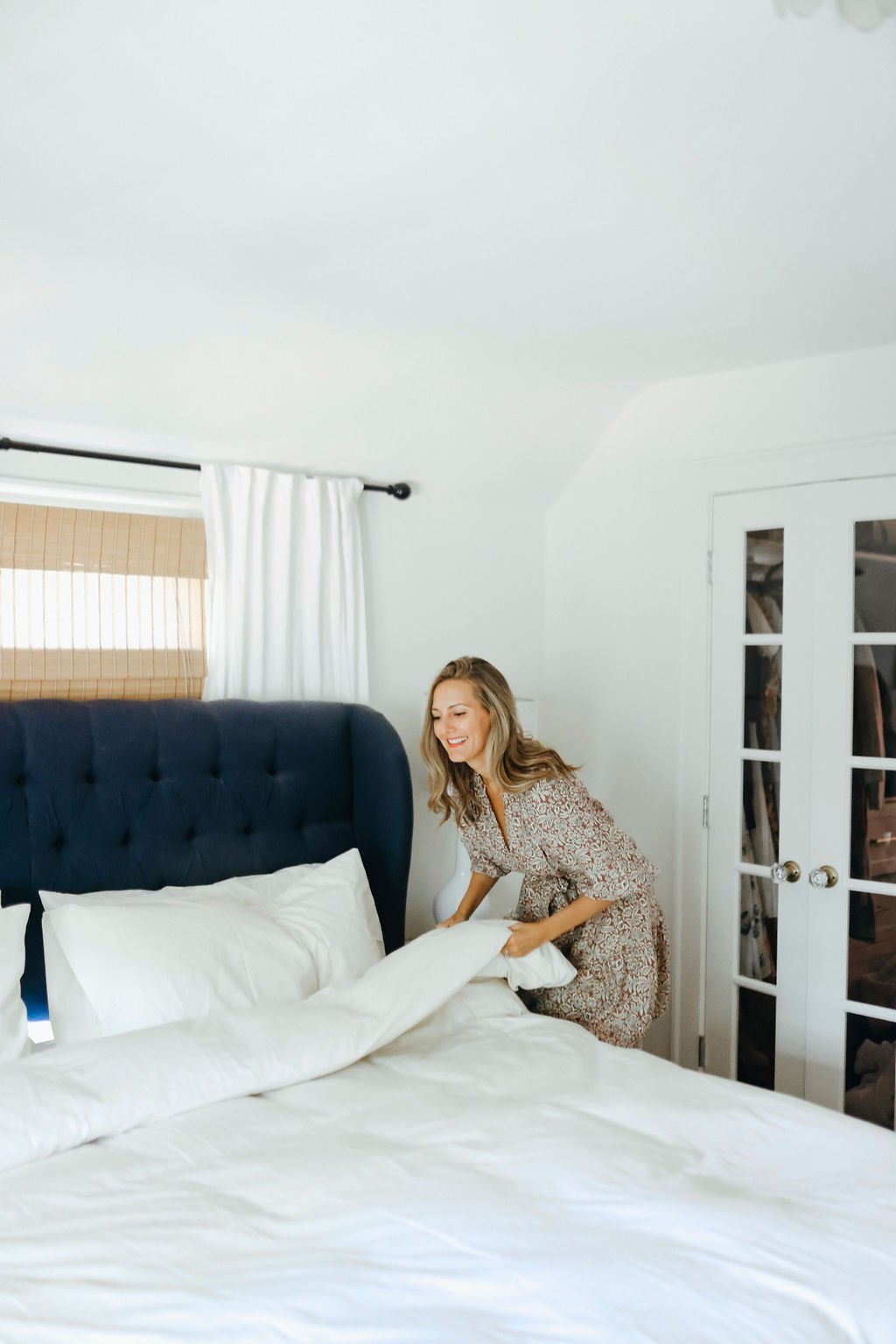 woman fixing the linens on her bed